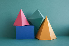 Colorful abstract geometric background with three-dimensional solid figures. Pyramid prism rectangular cube arranged on Stock Photography