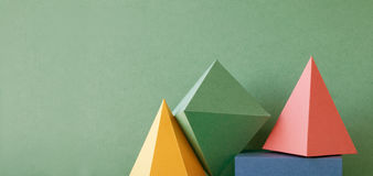 Colorful abstract geometric background with three-dimensional solid figures. Pyramid prism rectangular cube arranged on. Green paper. Yellow blue pink malachite Stock Photography