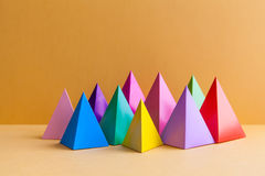 Colorful abstract geometric figures still life. Three-dimensional pyramid prism rectangular cube on orange background. Yellow blue pink green violet red royalty free stock image