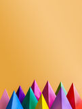 Colorful abstract geometric figures. Three-dimensional pyramid prism shapes, orange background. Yellow blue pink green. Violet red colored objects, textured stock photography