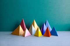 Colorful abstract geometric figures. Three-dimensional pyramid rectangular objects on green gray background. Yellow blue. Pink violet red colored tetrahedron Royalty Free Stock Photos