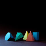 Colorful abstract geometric shape figures still life. Three-dimensional pyramid prism rectangular cube on black blue. Background. Yellow blue pink malachite stock photos