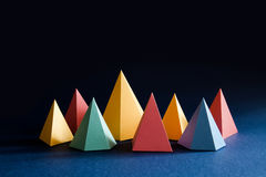 Colorful abstract geometric shape figures still life. Three-dimensional pyramid prism rectangular cube on black blue Stock Photo