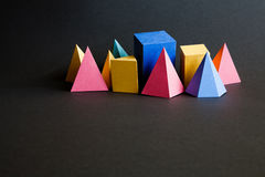 Colorful abstract geometric solid figures on black background. Pyramid prism rectangular cube yellow blue pink green Stock Photos
