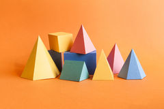 Colorful abstract geometrical composition. Three-dimensional prism pyramid rectangular cube objects on orange paper. Background. Yellow blue pink green colored royalty free stock image