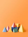 Colorful abstract geometrical composition. Three-dimensional prism pyramid rectangular cube objects on orange paper. Background. Yellow blue pink green colored stock photos