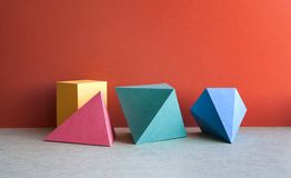 Colorful abstract geometrical composition. Three-dimensional prism pyramid tetrahedron rectangular cube objects on red. Gray paper background. Yellow blue pink Stock Photos