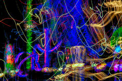 Colorful Abstract Light Streaks. Photographed with long exposure at night with amusement park rides in the background Stock Images