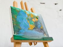 Colorful abstract painting in selective focus. Artistic picture on easel closeup, bright colors, art concept Royalty Free Stock Images