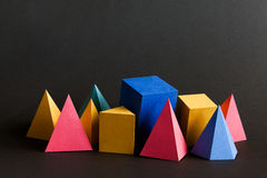 Colorful abstract solid figures composition. Three-dimensional prism pyramid rectangular cube geometric objects on black. Paper background. Red blue yellow stock photo