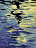 Colorful Abstracted Wave forms. Light reflecting on water waves, creating a beautiful abstract pattern of blue, gold and black Royalty Free Stock Images