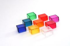 Colorful Acrylic Cubes. Nine small, colored acrylic boxes or cubes, artistically arranged in a 3 X 3 square on a white background stock photography