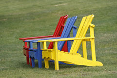 Colorful Adirondack chairs on green grass Stock Photos