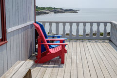Colorful Adirondack deck and beach chairs in bright red and brig Royalty Free Stock Photos