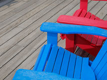 Colorful Adirondack deck and beach chairs in bright red and brig Royalty Free Stock Image