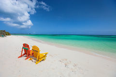 Colorful adirondack lounge chairs at Caribbean beach Stock Images