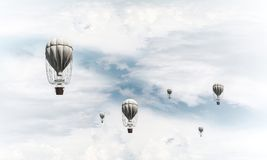Flying hot air balloons in the air. Colorful aerostats flying over the blue cloudy sky. 3D rendering royalty free stock images
