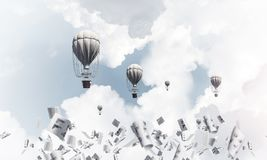 Flying hot air balloons in the air. Colorful aerostats flying among paper documents and over the blue cloudy sky. 3D rendering Royalty Free Stock Photos