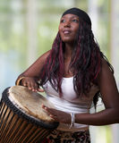 Colorful African Djembe Drummer. An African woman plays the djembe drum Stock Photo