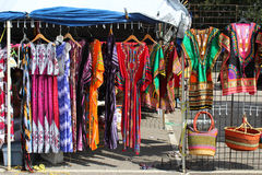Colorful African fashions at an outdoor flea market. Colorful print dresses, woven bags, and African dashikis hanging on a rack at an outdoor flea market stock photos