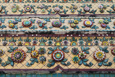 Colorful aged flower ceramic tile decoration at buddhist temple Stock Photo