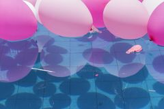 Colorful air balls. Colored balloons and mirrored by the pool after a family holiday. The sun reflects on the water of the pool being possible to visualize the Royalty Free Stock Image