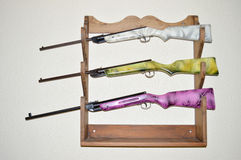 Colorful airbrushed old airguns in hand crafted gun rack Stock Image