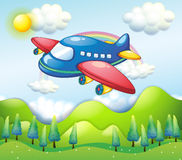A colorful airplane above the hills Stock Photos