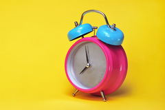 Colorful alarm clock. Brightly colored alarm clock of pink and blue reading nearly 8:00, isolated on a bright yellow background Stock Images