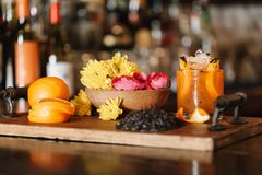 A colorful alcoholic rum cocktail with ingridients such as oranges, tumeric and black sesame seeds royalty free stock photography