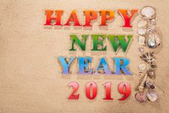 Colorful of alphabet happy new year 2019 on the beach. Decorate with shells with copy space royalty free stock photo