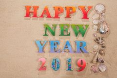 Colorful of alphabet happy new year 2019 on the beach. Decorate with shells with copy space stock images
