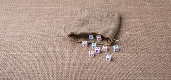 Colorful alphabet letter cubes out of sack. On a canvas Royalty Free Stock Images