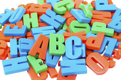Colorful alphabet letters on a magnet. On white background Stock Photos