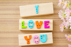 Colorful alphabet of LOVE wording on wooden background. Royalty Free Stock Images