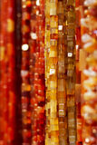 Colorful amber necklaces. Closeup of colorful red and amber necklaces, hung on market stall Stock Photography