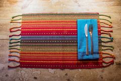 Colorful American Southwest inspired dinner place setting on a rustic wood table. Horizontal aspect Royalty Free Stock Photography