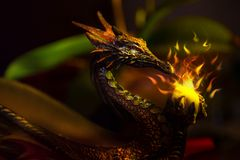 A colorful ancient dragon statue holding a sparkling ball of lig Royalty Free Stock Photo