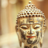 Colorful ancient head of Buddha smiling. Close up portrait of Buddha statue peeling off, square Stock Image