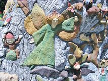 A colorful angel carved in a tree Stock Images