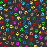Colorful animal paw prints seamless pattern. Multicolor animal paw prints seamless pattern background on dark background Stock Images