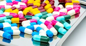 Colorful of antibiotic capsules pills with shadows on stainless steel drug tray. Drug resistance concept royalty free stock photos