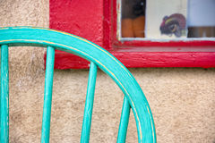 Colorful Antique Chair and Window. Turquoise colored antique chair sitting in front of a red window frame on Canyon Road in Santa Fe, NM royalty free stock photo