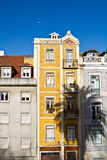 Colorful apartment building. Focus on a 4 story colorful traditional apartment building with shadow being cast by a palm tree. Lisbon, Portugal stock photography