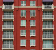 Colorful apartment building. Mid section of a red apartment building with balconies stock images