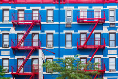 Colorful apartment building in NY with red fire escapes stock images