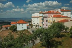 Colorful apartment buildings on hilltop. With countryside landscape and trees, in a sunny day at Gouveia. A nice country town with gardens and captivating royalty free stock image