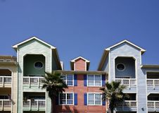Colorful apartments (condo). Beach style apartments (condo) with palms on blue sky background Stock Photos