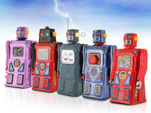 Colorful Army of Tin Toy Robots. Row of five tin toy robots against a blue sky and lightning Royalty Free Stock Photos