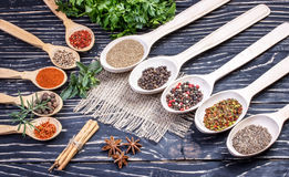 Colorful aromatic Indian spices and herbs on an old oak wooden deep blue board Stock Photos